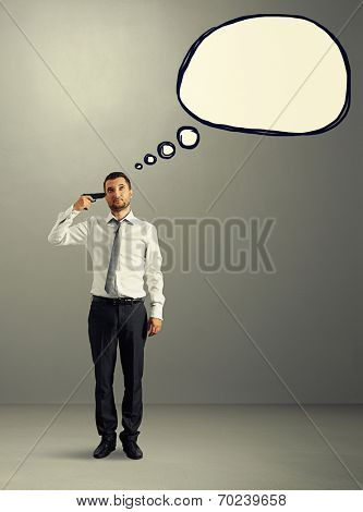 full length portrait of stressed businessman in formal wear with gun and empty speech balloon over grey background