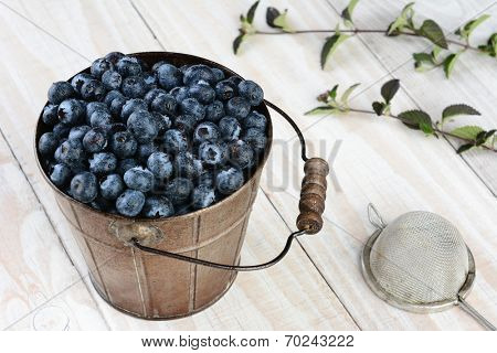 High angle shot of a metal bucket full of fresh picked blueberries on a rustic wooden kitchen table. Horizontal format with leaves and a strainer.