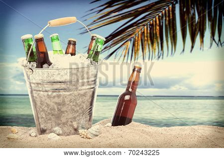 Assorted beer bottles in a bucket of ice in the sand on a tropical beach with an instagram look. One beer bottle without a cap is by itself stuck in the sand next to the pail.