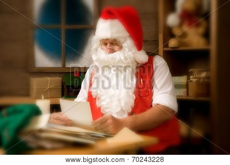 Santa Claus in his workshop reading letters and surrounded by toys and presents. Instagram feel with warm tones and vignette