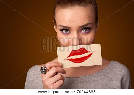 Happy pretty woman holding card with kiss lipstick mark on gradient background
