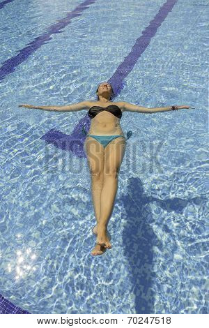 Young Woman Floating In The Swimming Pool