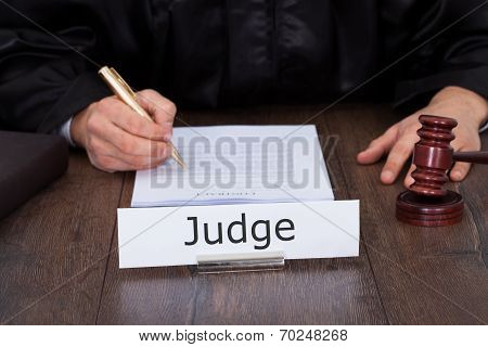 Judge Writing On Legal Documents