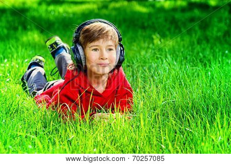 7 years old boy lying on a grass and listening to music in headphones. Summer day.