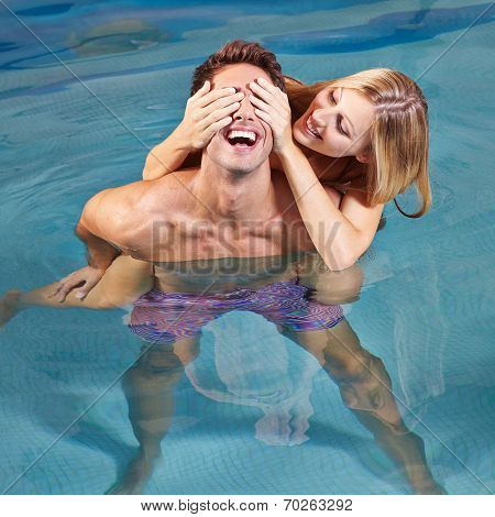 Happy young couple having fun togther in swimming pool in summer