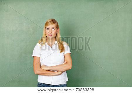 Blond pensive woman as teacher standing in front of chalkboard