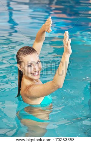 Woman doing back training in water in aqua fitness class