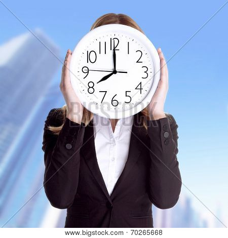 Business woman wearing formal suit and holding big clock on face, standing outdoors on office building background, punctual worker concept