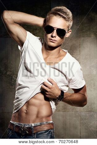 Handsome young man. Portrait on cheerful sexy guy wearing sunglasses