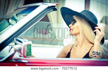 Outdoor summer portrait of stylish blonde vintage woman driving a convertible red retro car