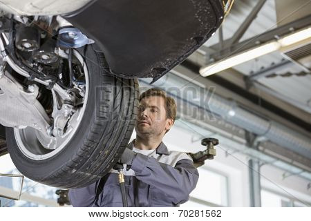 Mid adult technician repairing car's wheel in workshop
