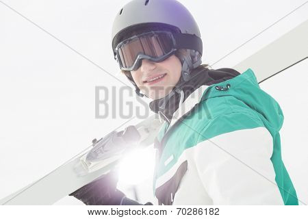 Portrait of smiling young man carrying skis against clear sky