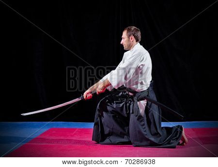 Martial arts fighter with katana on black