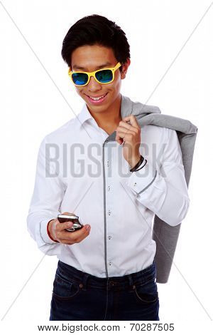 Fashion asian man in sunglasses using smarthone over white background