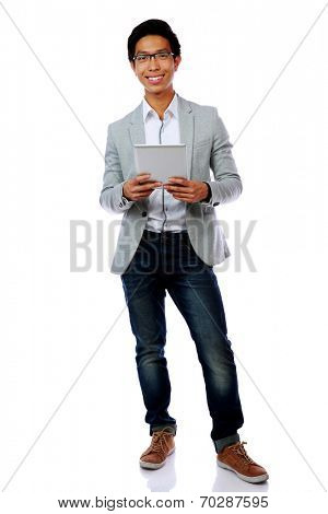 Full length portrait of a happy asian man holding tablet computer over white background