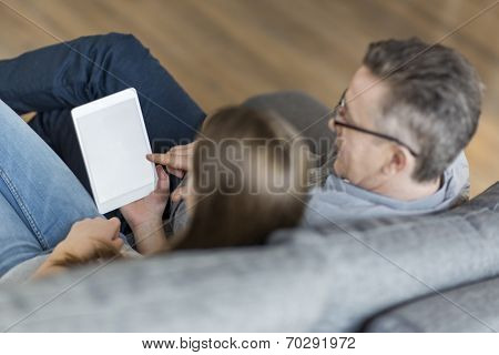 High angle view of father and daughter using digital tablet on sofa