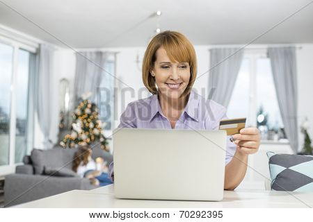Happy woman shopping online at home during Christmas