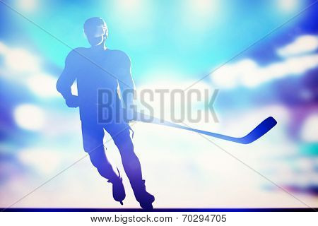 Hockey player skating on ice in full arena night lights