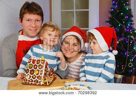 Father, Mother And Two Little Sons With Selfmade Gingerbread Cookie House