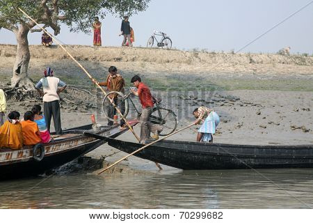 GOSABA, INDIA - JANUARY 19: wooden boat crosses the Ganges River January 19, 2009 in Gosaba, West Bengal, India. To use a small wooden is easy, fast and cheap way how to cross the Ganges River.