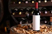 picture of wine cellar  - Bottle of red wine with blank label template and glass standing in a wine cellar on a wood barrel - JPG