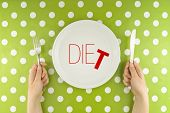 stock photo of knife  - Female hands at dinner table holding fork and a knife above plate as dieting concept - JPG