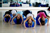 stock photo of bending over backwards  - People at the gym bending backwards over a pilates ball - JPG