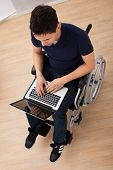 image of handicap  - Full length of young handicapped man using laptop while sitting on wheelchair at home - JPG