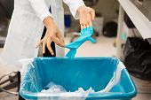 stock photo of garbage bin  - Closeup cropped portrait healthcare professional throwing away blue disposable latex gloves in trash - JPG