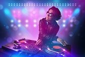 image of disc jockey  - Young disc jockey mixing music on turntables on stage with lights and stroboscopes - JPG