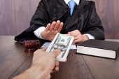 stock photo of take responsibility  - Midsection of judge refusing to take a bribe from client at desk in courtroom - JPG