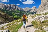 stock photo of south tyrol  - hiker on footpath in Sella mountain on background Colfosco and Badia Valley south Tyrol Italy - JPG
