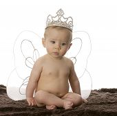 stock photo of toddlers tiaras  - seven month old baby sitting cross legged wearing angel wings - JPG
