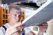 stock photo of dungarees  - Young handyman during work at kitchen horizontal - JPG