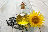 foto of sunflower-seeds  - Sunflower oil in bottles with seeds and flower on wooden background