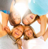 image of huddle  - Group of Four Teenage Girls having fun outdoors - JPG
