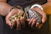 image of grenades  - handcuffed hands holding ammunitions and a grenade - JPG