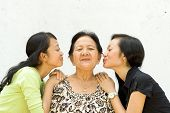 stock photo of ethnic group  - asian family portrait of two teen girls show their love to their old grandmother - JPG