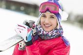 picture of cold-shoulder  - Beautiful young woman carrying skis in snow - JPG