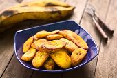stock photo of plantain  - Fried slices of the ripe plantain in blue bowl which can be eaten as snack or is used to accompany dishes in some South American countries ripe plantains in the back  - JPG