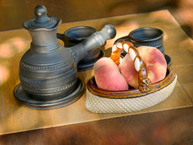 stock photo of loamy  - Coffee set and ceramic vase with peaches on a table - JPG