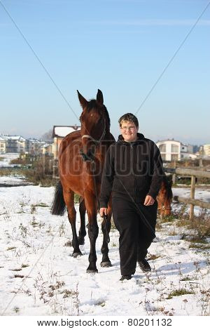 Teenager Boy And Brown Horse Walking In The Snow
