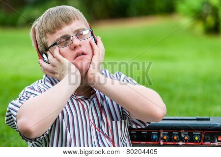 Handicapped Boy Enjoying Music On Head Phones.