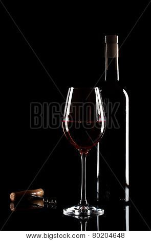 Glass of red wine, bottle and corkscrew