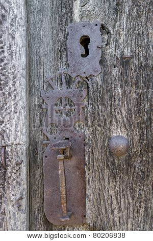 Old run-down wooden door and decorated iron lock