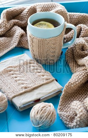 A Cup Of Tea With Lemon In Sweater,  Old Notebook, Beige Knitted Blanket And Spokes