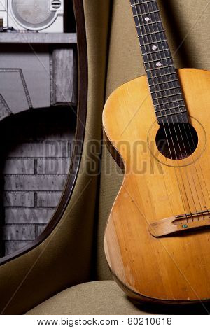 Acoustic Guitar On Chair Against The Brickwork