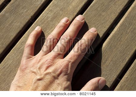 Man Hand Over Sunny Teak Wood Lines