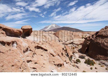 Volcanic rock and Ollague volcano in Atacama desert