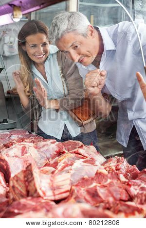 Mature couple looking at meat through display cabinet in butchery
